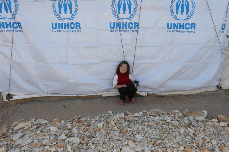 فتاة سورية صغيرة تجلس بجانب كومة خبز مجفف بمخيم للاجئين في عكار بلبنان | المصدر: رويترز/ محمد عزاقير