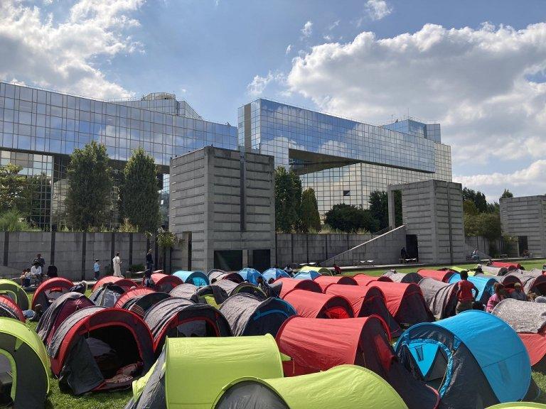 """خيام المهاجرين المنتشرة في حديقة """"أندريه سيتروان"""" قبالة مبنى محافظة باريس في الدائرة 15 للعاصمة الفرنسية، 1 أيلول/سبتمبر 2021. الصورة من حساب منظمة """"يوتوبيا 56"""" على تويتر"""