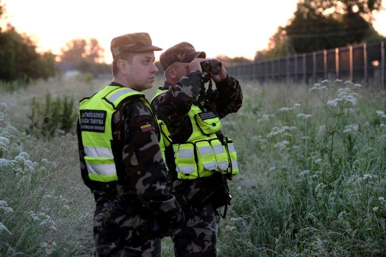 عناصران من حرس الحدود الليتواني يستخدمان مناظير حرارية لمراقبة الحدود مع بيلاروسيا، بالقرب من أدوتيسكيس في ليتوانيا، 15 حزيران\يونيو 2021. رويترز