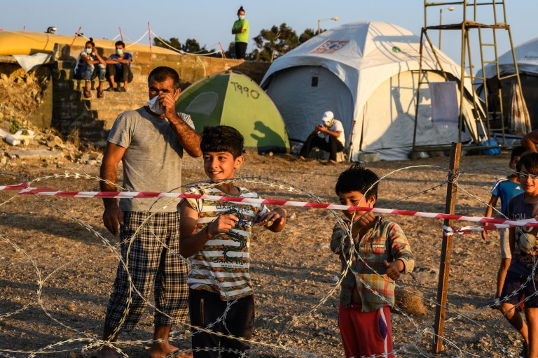 Adults and minors refugees and migrants stand behind razor wire at Kara Tepe camp on Lesbos island, Greece on September 19, 2020 | Photo: EPA/Vangelis Papantonis