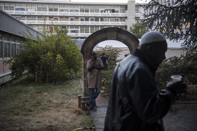 Migrants wait in the yard of an unoccupied building of the 'Agence nationale pour la formation professionnelle des adultes' (AFPA), in the Paris suburb of Montreuil. Photo: EPA/JULIEN DE ROSA
