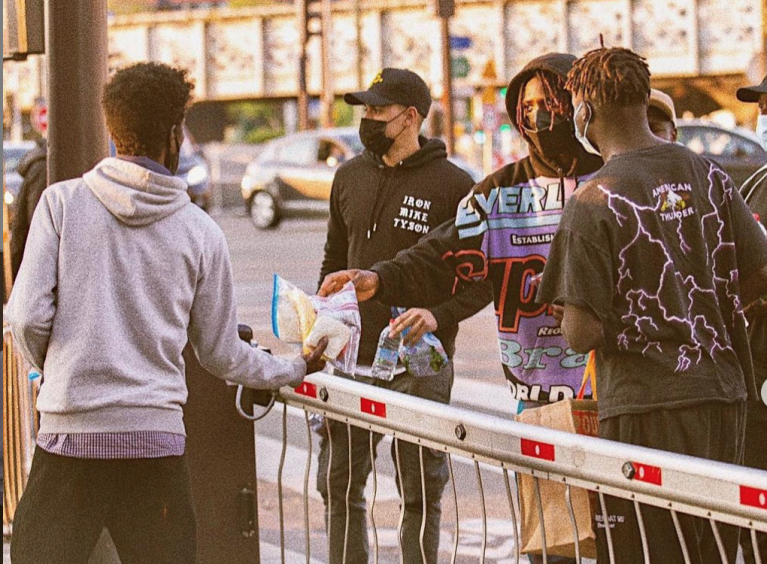 Moise Kean, joueur du PSG, au centre, distribue de la nourriture aux migrants dans le nord de Paris. Crédit : capture d'écran du compte Instagram de Moise Kean