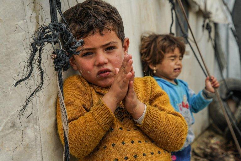 ANSA / أطفال نازحون يقفون إلى جوار خيمتهم داخل مخيم خربة الجوز في ريف إدلب بسوريا. المصدر: إي بي إيه / يحيى نعمة.