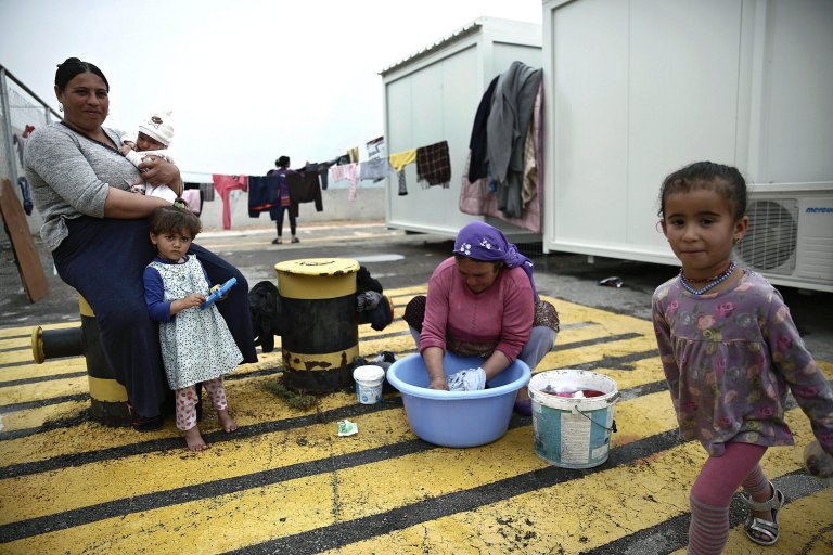 A woman washing clothes outside containers hosting migrants and refugees in a new facility in Skaramangas, near Athens, Greece | Credit: ARCHIVE/EPA/SIMELA PANTZARTZI