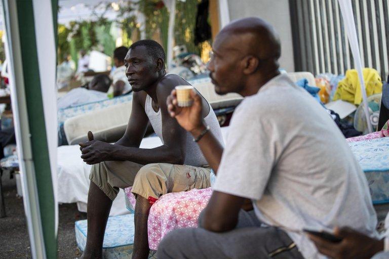 Ansa مهاجرون في شارع سكورتيكابوفي حيث كانت تقيم مجموعة من اللاجئين.
