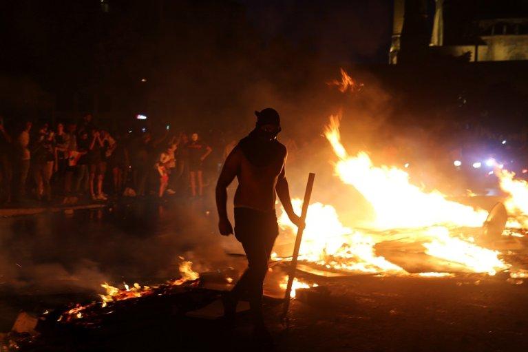 متظاهر بالقرب من عدد من الإطارات المشتعلة بالقرب من وسط بيروت التجاري خلال مسيرة احتجاجية اندلعت رفضا لتدهور الأوضاع الاقتصادية والمعيشية في لبنان. بيروت 18 تشرين الأول/أكتوبر 2019. رويترز