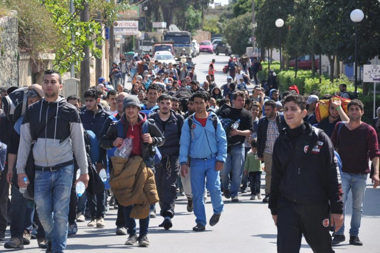 Migrants walk in a street of Chios city, on Chios island, Greece. Credit: EPA/ORESTIS PANAGIOTOU