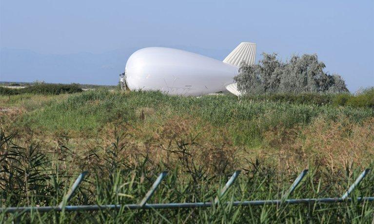 """نظام بالون هوائي تابع لـ""""وكالة الحدود"""" التابعة للاتحاد الأوروبي """"فرونتكس""""، مزود بكاميرات مراقبة عالية التقنية، في مطار ألكسندروبوليس ، اليونان - 28 تموز 2021 (رويترز)"""
