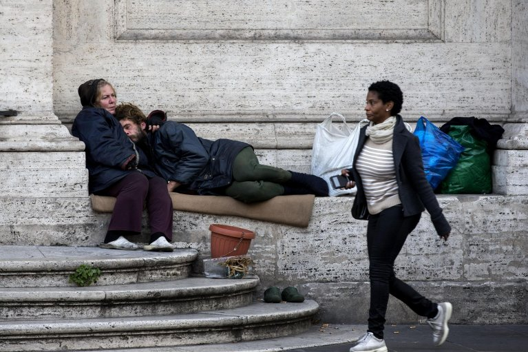 Homeless people sitting in front of a church in Rome | Photo: ANSA/Massimo Percossi