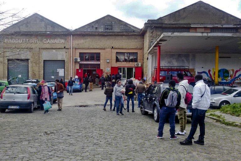 """مهاجرون أمام المنشأة التي تستضيف المركز الاجتماعي """"إكس بانافيشيو""""، وهي المؤسسة التي تدير نظام استضافة طالبي اللجوء في كاسيرتا. المصدر: أنسا / أنطونيو بيسان."""
