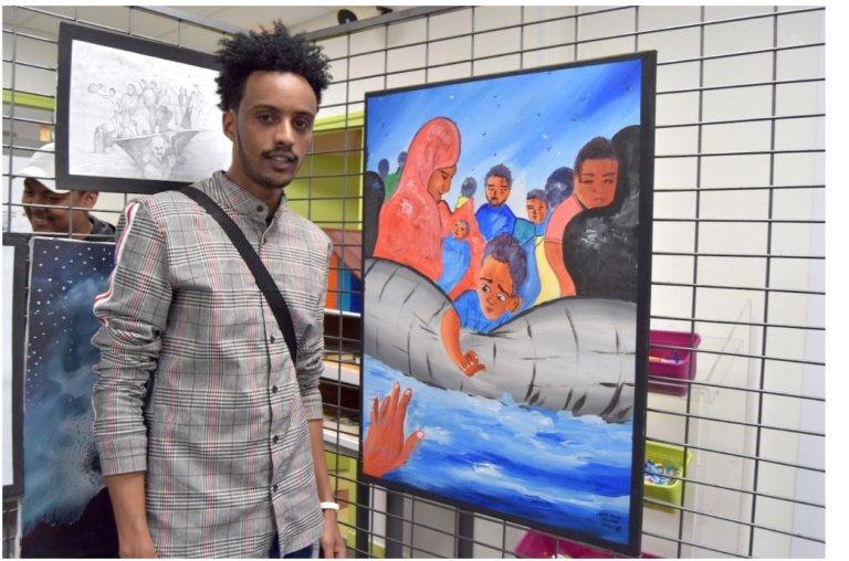 الفنان اللاجئ منير حسن أمام لوحته التي تحكي مغامرته في البحر المتوسط