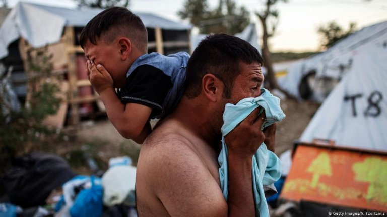 A man and boy crying after a fire and clashes broke out at the Moria refugee camp | Photo: Getty Images/A.Tzortzinis