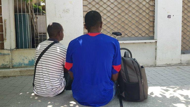 Thierry (à droite) et un ami sont assis devant le centre pour migrants de Caritas à Nicosie. Ils y viennent pour sociabiliser et recevoir du soutien dans leur procédure de demande d'asile. Crédit : Anne-Diandra Louarn / InfoMigrants