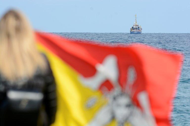 امرأة تحمل علم صقلية وتنظر إلى سفينة الإغاثة Sea-Watch 3 العالقة في البحر المتوسط وعلى متنها 47 مهاجرا قبالة سواحل مدينة سيراكوزا في جزيرة صقلية 26 يناير 2018 | المصدر: رويترز