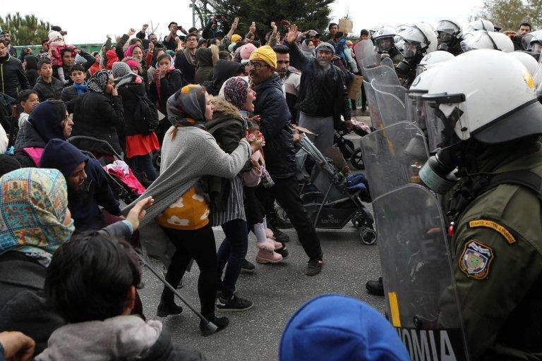 REUTERS/Elias Marcou  Des exilés face à la police anti-émeute, à l'extérieur du camp de Kara Tepe, sur l'île de Lesbos, le 3 février 2020.