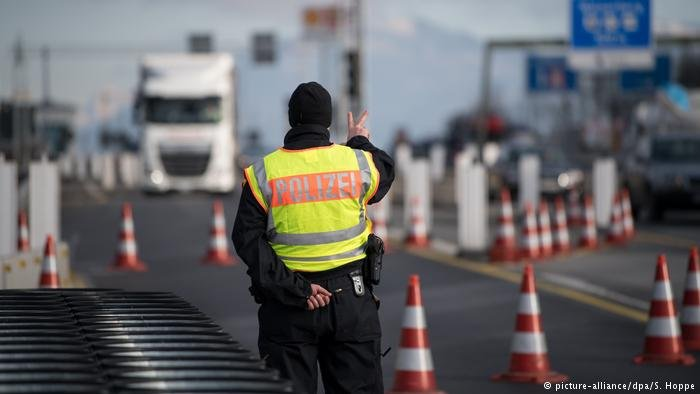 A German police officer signals to vehicles near the border with Austria