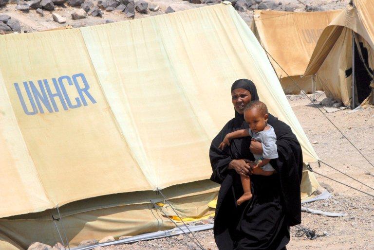 """ansa / لاجئة صومالية تحمل طفلا وهي تسير أمام خيمة المساعدات التابعة للأمم المتحدة، في مخيم """"خاراز"""" للمهاجرين في مدينة عدن اليمنية."""