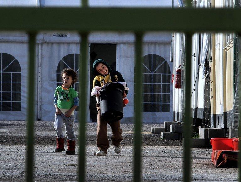 """ansa / طفل يحمل سلة مليئة بالغسيل في مركز استقبال المهاجرين في ضاحية إيلايوناس بالعاصمة اليونانية أثينا. المصدر: صورة من أرشيف """"إي بي إيه""""."""