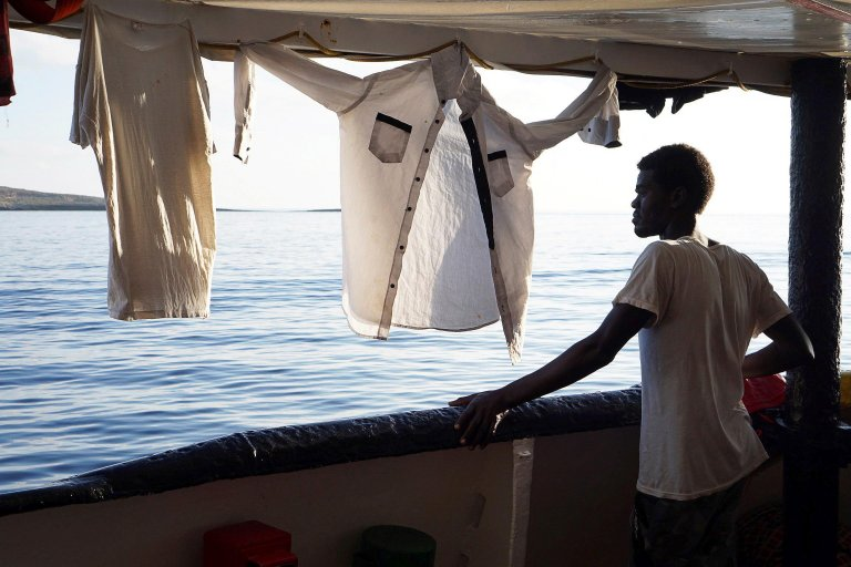 A migrant onboard the rescue vessel Open Arms looks towards the Italian coast on August 18, 2019 | Photo: EPA/Fransisco Gentico