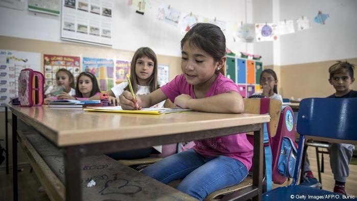 A refugee from Afghanistan in a classroom   Photo via DW: Getty Images/AFP/O.Bunic