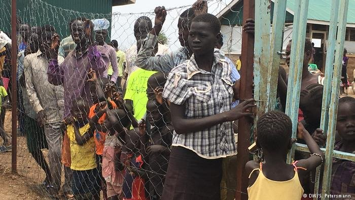 Refugees wait at the gate of the transit camp between Kenya and South Sudan