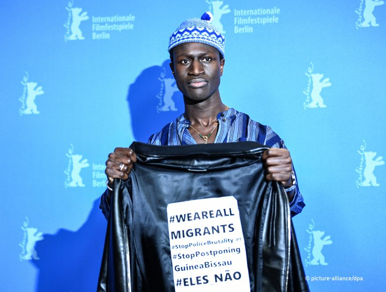 """Actor Welket Bunguê holds up a jacket with a clear message at the Berlinale premiere of """"Berlin Alexanderplatz"""" 