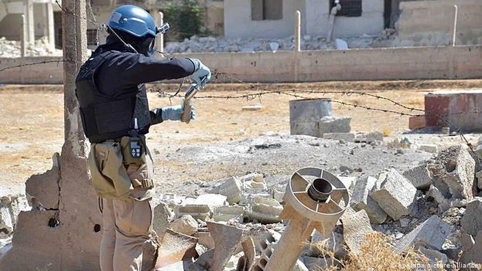 أحد افراد بعثة الأمم المتحدة يقوم بجمع عينات مما يعتقد أنه صاروخ أطلقة الجيش السوري وكان يحمل غاز السارين