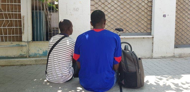 Thierry (à droite) et un de ses amis guinéens devant le centre de Caritas. Crédit : Anne-Diandra Louarn