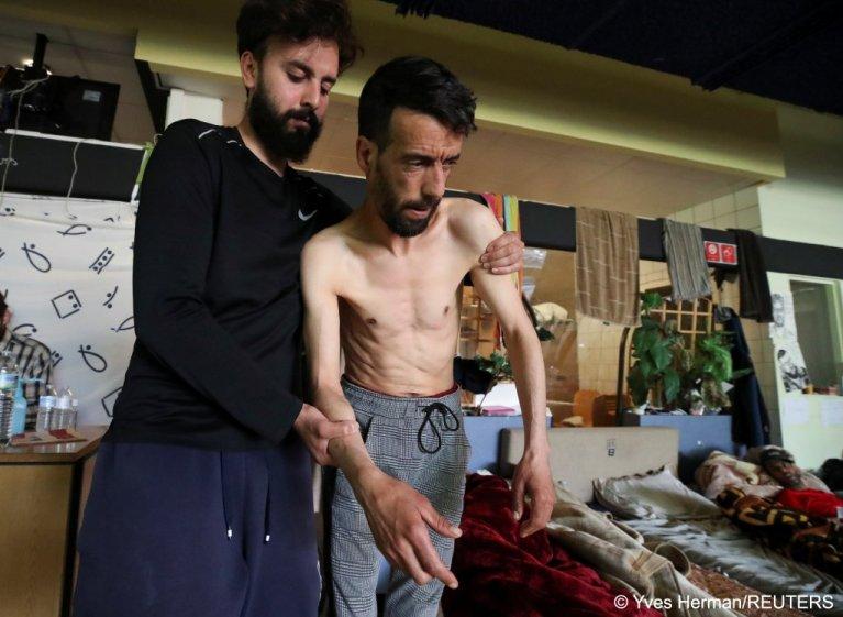 """يوسيف بوزيدي، طالب لجوء مغربي مضرب عن الطعام منذ أكثر من شهر، يساعده أحد المتطوعين على الانتقال من مكانه في حرم """"جامعة بلجيكا الحرة"""" في بروكسل، 29 حزيران/يونيو 2021. رويترز"""