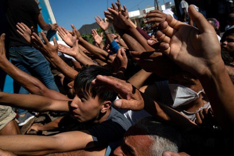 REUTERS/Alkis Konstantinidis |Des réfugiés et demandeurs d'asile tendent la main pour recevoir des tomates lors d'une distribution de nourriture au camp incendié de Moria, à Lesbos, le 10 septembre 2020.