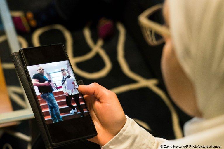 Faeza Satouf looks at a photo of her graduation day in Nivaa, Denmark, April 21, 2021 | Photo: AP Photo/David Keyton