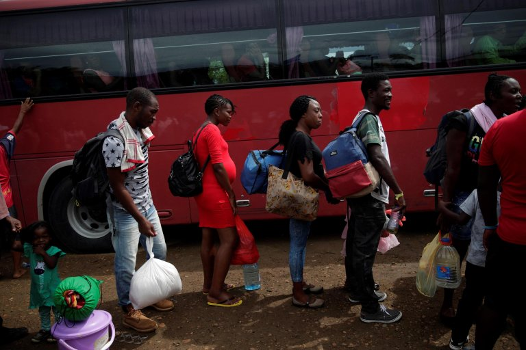 Migrants line up to get on a bus to Costa Rica from a temporary humanitarian campsite in the village of Penita, Panama | Photo: EPA/Bienvenido Velasco