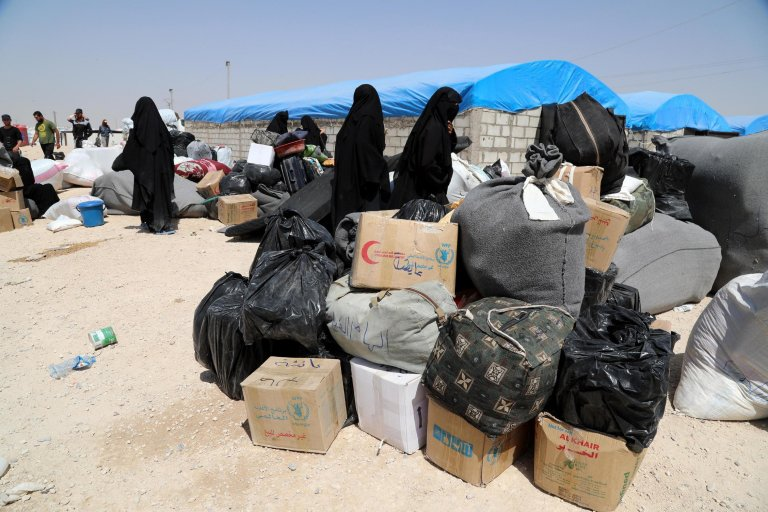 Wives of Islamic (IS) state fighters wait next to their belongings upon their deportation from the al-Hol camp for refugees, Syria | Photo: Ahmed Mardnli/EPA