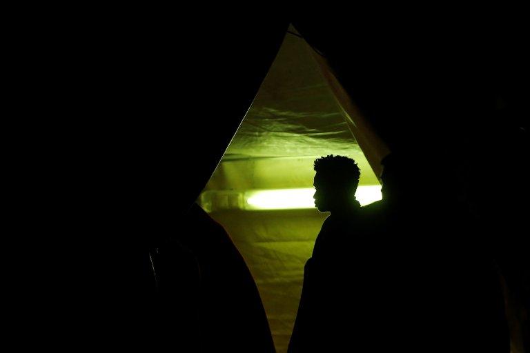 مهاجر تم انقاذه في البحر الأبيض المتوسط قبالة سواحل إسبانيا، يدخل خيمة للصليب الأحمر الاسباني بعد وصوله إلى ميناء ملقة قبل أيام قليلة / رويترز