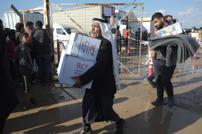 Iraqi displaced people receive donations from the Barzani Charity Foundation after their refugee camp - Salamiya 3, southeast of Mosul - was flooded following heavy rainfall | Photo: EPA/GAILAN HAJI