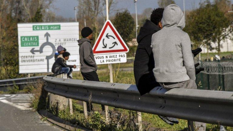 Philippe Huguen, AFP |Des migrants assis sur une barrière le long de la route menant au port de Calais, le 2 novembre 2017.