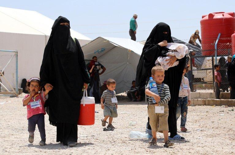 ANSA / زوجات لمقاتلين من داعش يسرن مع أطفالهن في مخيم الهول بمحافظة الحسكة، في شمال شرق سوريا. المصدر: إي بي إيه/ أحمد ماردنلي.