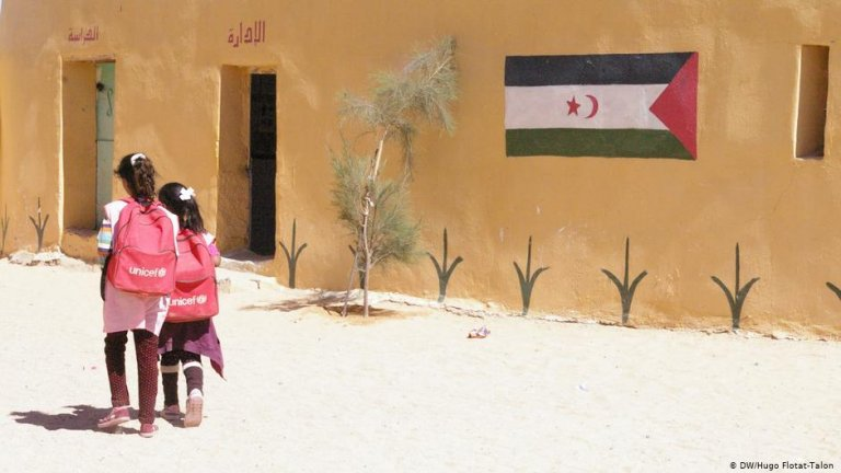 Two young girls carrying red UNICEF backpacks walk side by side | Photo: DW/Hugo Flotat-Talon