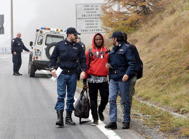 Un migrant entouré de policiers à la frontière franco-italienne. Crédit : Credit: ANSA/ALESSANDRO DI MARCO