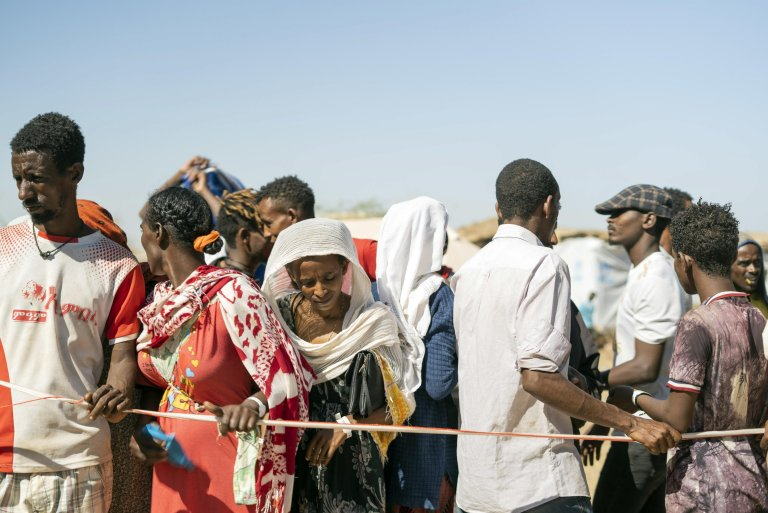 Ethiopian refugees from Tigray region wait to receive aid at the Um Rakuba refugee camp, some 80 kilometers from the Ethiopian-Sudan border in Sudan, 30 November 2020 | Photo: EPA/ALA KHEIR