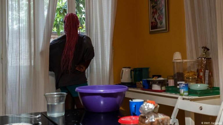 """طالبة لجوء شابة تنظر من النافذة إلى ملجأ للسيدات والمهاجرات غير المصحوبات  بذويهن والذي تديره منظمة """"مشروع المنزل"""" في أثينا"""