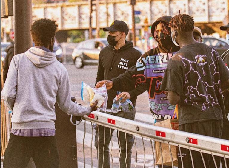 """مويز كين، مهاجم فريق """"باريس سان جيرمان""""، يوزع الطعام على مهاجرين، شمال باريس. المصدر: صفحة اللاعب على أنستغرام"""