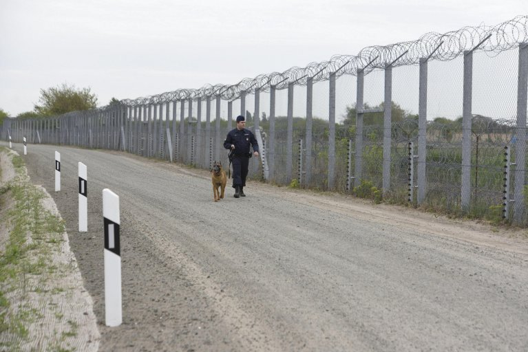 A police officer patrols the temporary border fence along the Hungary-Serbia border near Roszke, 180 kilometers southeast of Budapest, Hungary | Photo: EPA/ZOLTAN GERGELY KELEMAN