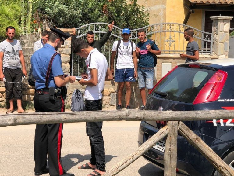 A police officer with migrants hosted at the center of Monastir, in Sardinia | Photo: ANSA