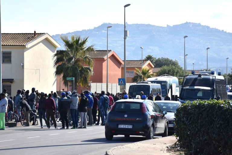 One of the buses arrives to transfer the first migrants from Mineo to Trapani. | PHOTO: ANSA/Orietta Scardino