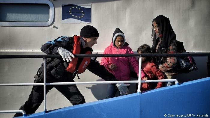 A coastguard helps migrant children disembarking from a Bulgarian FRONTEX ship in Mytilene