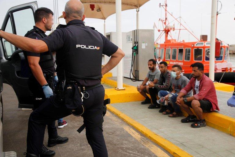ANSA / ضباط الشرطة الإسبانية يراقبون 4 مهاجرين وصلوا على متن قارب لجزيرة شافاريناس في مليلية، الجيب الإسباني في شمال شرق المغرب. المصدر: إي بي إيه / أف جي جوريرو.