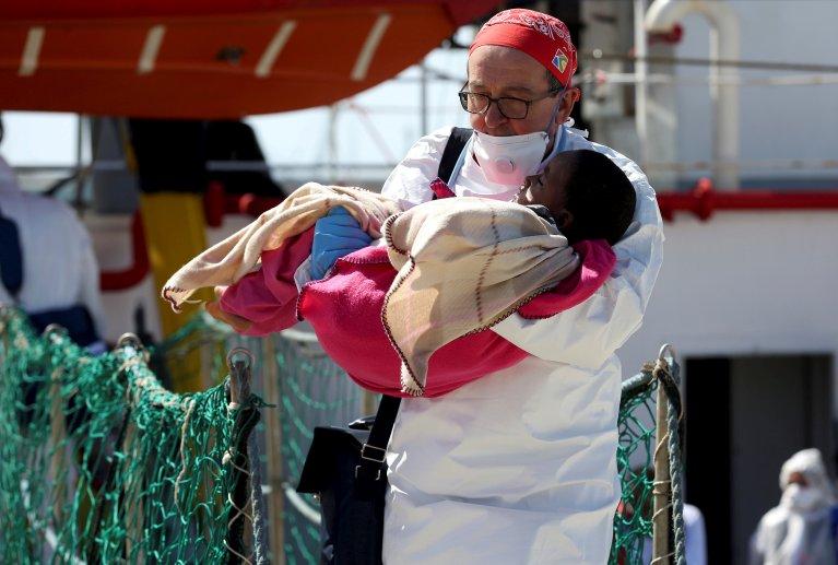 REUTERS/Antonio Parrinello |Un médecin de MSF avec un enfant secourus en mer débarque à Pozzallo, en Sicile, en avril 2016.