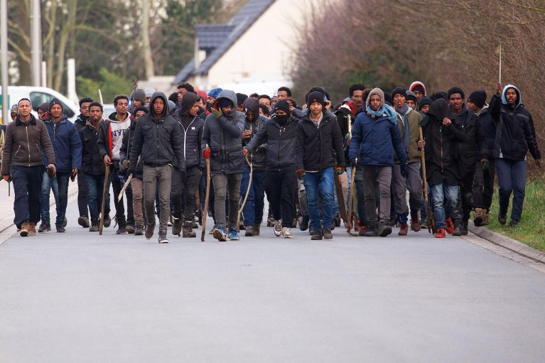 This picture shows a group of migrants carrying sticks during clashes near the ferry port in Calais, northen France. Photo/Archive/EPA/Johan ben Azzouz