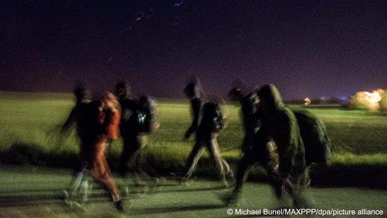 لاجئون يمشون ليلاً لمحاولة عبور الحدود بين صربيا ورومانيا بالقرب من بلدة مجدان الصربية